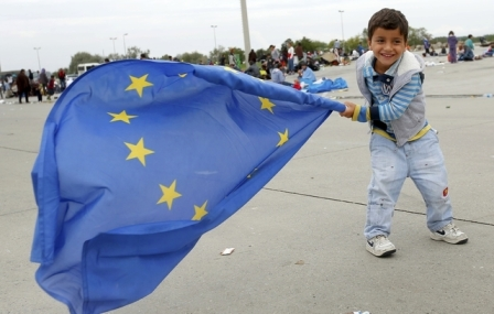 A young migrant child plays with a European Union flag after crossing the Austrian border in Nickelsdorf September 5, 2015. Thousands of exhausted migrants streamed into Austria on Saturday, bussed to the border by a Hungarian government that gave up trying to hold them back as Europe's asylum system buckled under pressure from the numbers reaching its frontiers. Austrian police said 2,000 had arrived at the border, with many more likely to follow during the day. Trains were laid on to take them from the border town of Nickelsdorf to Vienna. REUTERS/Laszlo Balogh